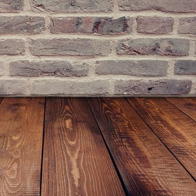 Mörkt trägolv och tegelvägg